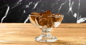 refreshment time : chocolate ice cream blocks melting in a cup with timelapse
