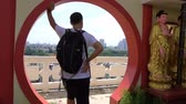 kapualj : Caucasian man enjoy panorama city view from round doorway of Chinese temple
