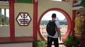 Caucasian man enjoy panorama city view from round doorway of Chinese temple
