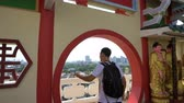 vstoupit : Caucasian man enjoy panorama city view from round doorway of Chinese temple