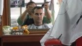 saloon : Female barber cut hair of caucasian man in Asian barbershop. Mirror reflection