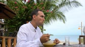 Young caucasian businessman having meal on tropical beach with sea view