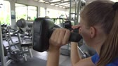 súly : Young woman building triceps and biceps at gym