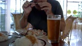 Close up of man eating fish and drinking beer