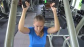 Young woman building arms and shoulders at gym