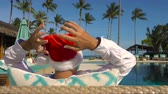 papai noel : Man in Santa Claus Hat by Pool. Celebrating New Year and Christmas in Hot Country