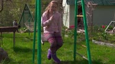 attentiveness : Danger! Girl on swing with fork in her mouth. Social problems. Slow-Mo Stock Footage