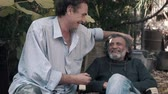 Two friends, father and son laughing while sitting outdoors