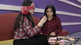 make : Two latina Teens Cover Their Eyes and make a make-up. Brunette girls make a make-up with their eyes closed