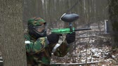 arma : A man in camouflage uniform and a protective mask shoots with an air gun. Paintball Game Vídeos