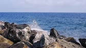 Blue sea waves crashing into big rocks, sunny day in Italy