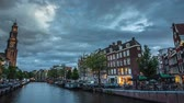 The most famous canals and embankments of Amsterdam city during sunset. General view of the cityscape and traditional Netherlands architecture. 4K Time Lapse Footage.