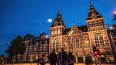 Amsterdam at summer night. Famous national Rijks museum general front view with moving tourist and different kind of transport. The Netherlands. 4K Time Lapse. Vidéos Libres De Droits