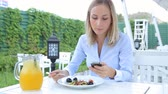 Beautiful woman using smartphone and eating salad in cafe