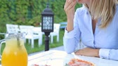Young couple eating pizza in the restaurant, outdoors Stok Video