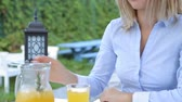 orangejuice : Blond woman pouring juice in a glass and drinks