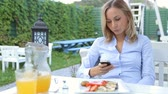 Attractive young woman at an outdoor table using her smart phone
