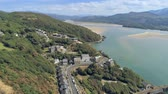 ardósia : Aerial view, tilt up and zoom in move. Drone panorama over sea, tree, hills and houses, Barmouth, Wales Vídeos