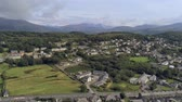 green area : Aerial view, landing, down move. Drone panorama of Penrhyndeudraeth town in Snowdonia mountains in Wales