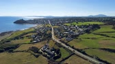 Уэльс : Aerial view, pan move. Drone panorama of sea with silhouette of Criccieth castle, grass fields, road and town in background
