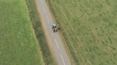 jazyk : Aerial view, down move and pan. Converted tractor with trimmer trims hedges on straight road between fields