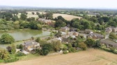 horizonte sobre a água : Aerial view, sideways move. Christleton houses next to pond. Village in Cheshire countryside.