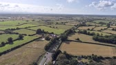 dual : Aerial view, down move. Traffic on road, houses and fields on Cheshire countryside Stock Footage