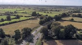 dual : Aerial view, zoom in and down move. Cars on road, houses among trees and fields on Cheshire countryside Stock Footage