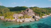 luxus : Aerial drone circle 4k footage of the most beautiful Anse Source Dargent beach on La Digue island, Seychelles. Warm sunset light