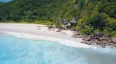 雄大な : 4K drone side flight above turquoise crystal clear ocean water and powerful surf on tropical paradise beach sandy Petite Anse, La Digue Island, Seychelles
