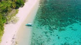 Aerial view. First tourist arrived on tropical sandy beach of Helicopter island, El Nido, Palawan Philippines. Turquoise blue lagoon with pure clear water best snorkeling place to see coral reef