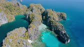 calcário : Aerial view of small and big lagoon on Miniloc Island. El-Nido, Palawan. Philippines. Limestone rock formation overgrown with plants and blue shallow bays in tour A