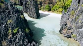 Aerial drone view over clear shallow lagoon water surrounded by sharp rocky formations. Hidden Beach, El Nido Palawan National Park Philippines. Summer tourist destination