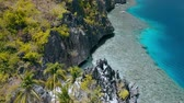 Aerial fly over Matinloc Shrine along the coastline. El Nido, Palawan, Philippines. Bizarre limestone mountain rocks and coral reef und crystal clear blue water. Sightseeing of Hopping island Tour C