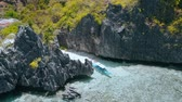 Aerial circling movement around Matinloc Shrine. El Nido, Palawan, Philippines. Bizarre limestone rocks and lonely boat in shallow water with colorful coral reef. Tour C Stock Footage