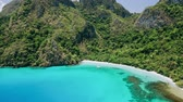 canoe : Aerial footage of empty tropical beach and amazing blue bay Cadlao lagoon. El-Nido. Palawan. Philippines