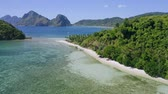 seascape : 4k Aerial drone fly above las cabanas sandy beach with palm trees. El Nido in background. Palawan, Philippines