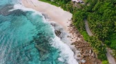 palma : Aerial view of waves breaking on the rocks and white beaches surrounded by coconut palm trees at Anse Bazarca, on Mahe Island, Seychelles Stock Footage