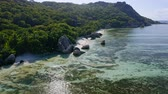 雄大な : Aerial footage fly along famous Anse Source dArgent tropical beach with unique granite boulders. Sunshine reflect on shallow lagoon surface at low tide. La Digue Island, Seychelles