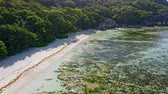 雄大な : Aerial footage of tropical paradise beach Anse Source dArgent. Shallow lagoon with beautiful algae pattern, granite rocks and rainforest around in morning sun light. La Digue Island, Seychelles 動画素材