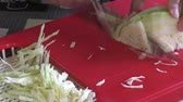 finely : The woman cuts cabbage on a red board