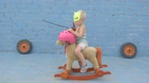 hrdina : Funny boy blond in superhero mask is sitting on toy rocking horse. child is armed with sword and signal horn and dreams of adventures, travels, exploits. Concept training of spirit, patriotizm