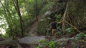 White man going down from a rock in jungles Stock Footage