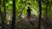 Man walks into shot and sits down on a big stone on top of a rock in jungles.