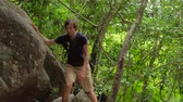 tourist climbing up the rocks in jungles