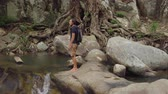 Tourist crosses a small river in jungles. Stock Footage