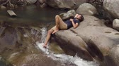 tourist lies on river bank in jungles with his foot in the river