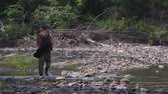 Fisherman in a waders walks a wild river side