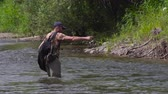 Man fishing on a mountain river with a ultralight spinning using fishing wobblers. Stock Footage