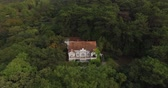 fotografia : aerial photography of a house in the forest, people walking near the house